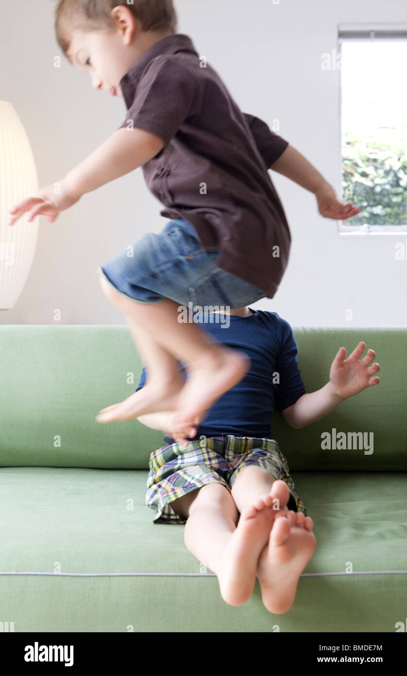 Young boy jumping over his brother on sofa - Stock Image