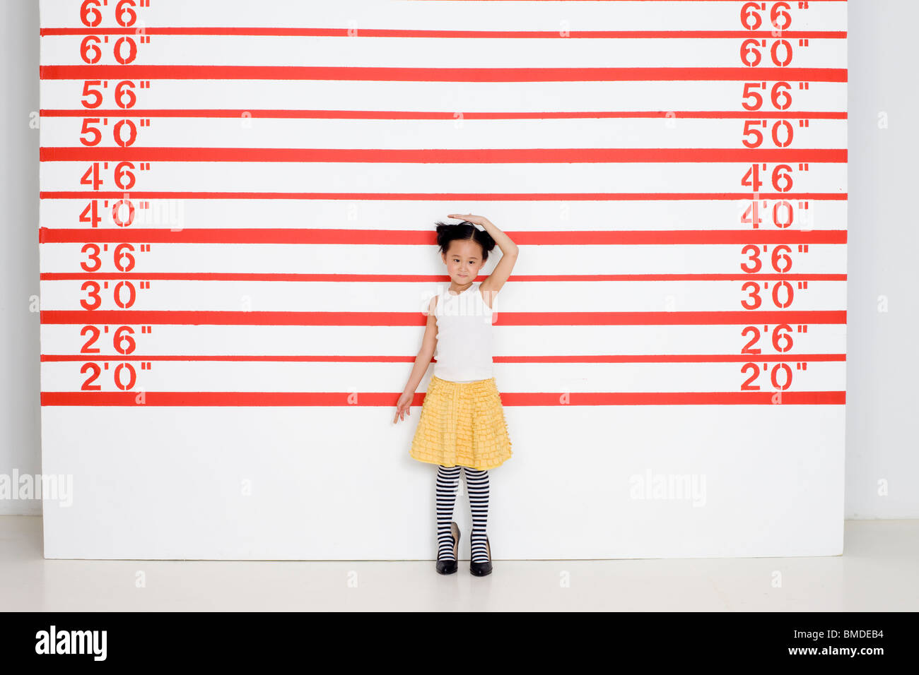 Girl in high heels measuring herself in front of growth chart - Stock Image