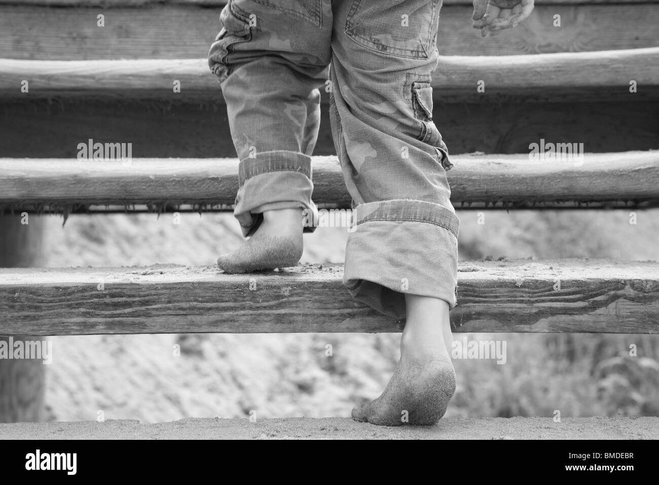 Young boy with sandy feet going up wooden stairs - Stock Image