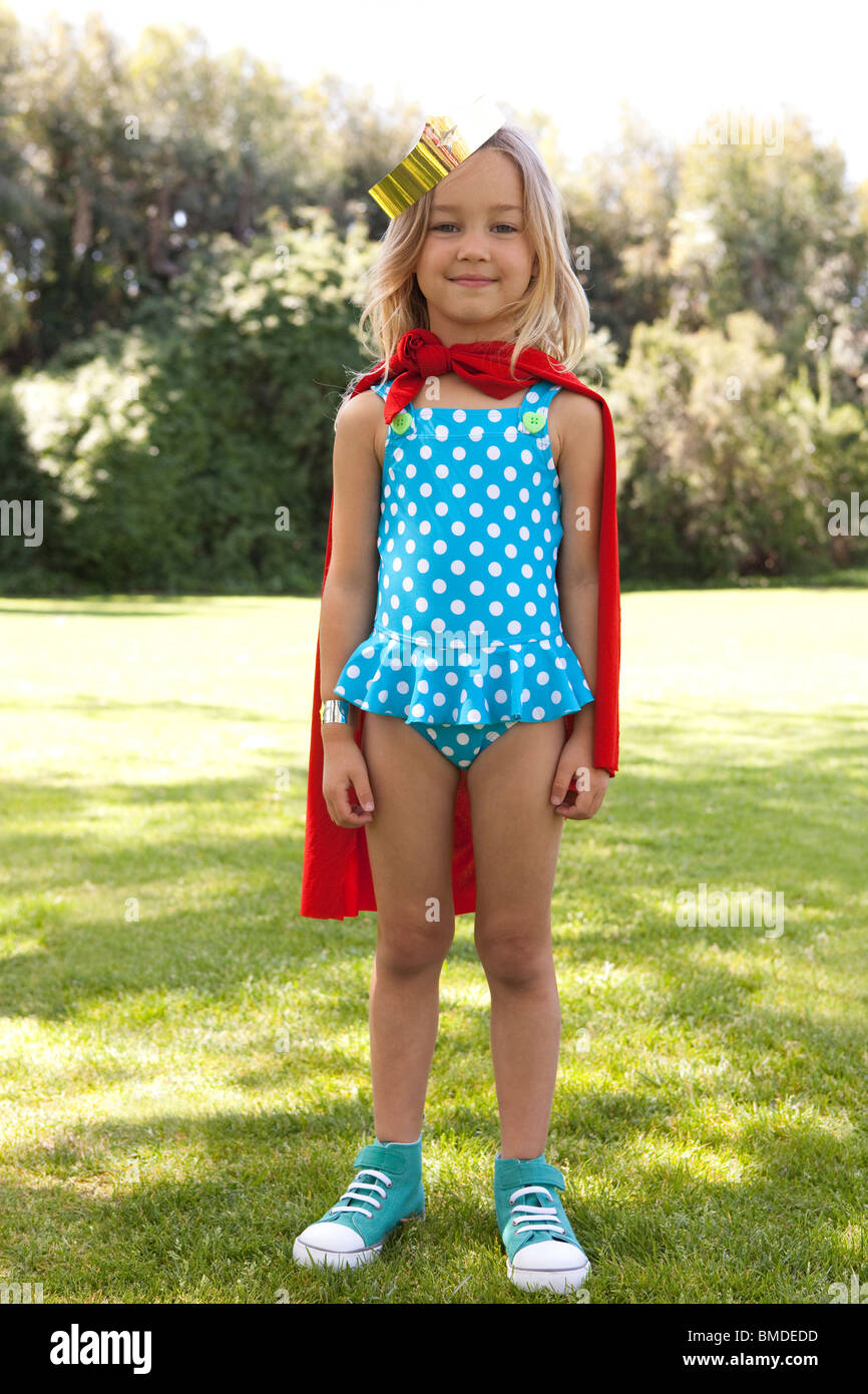Girl in polka dot bathing suit and red cape - Stock Image