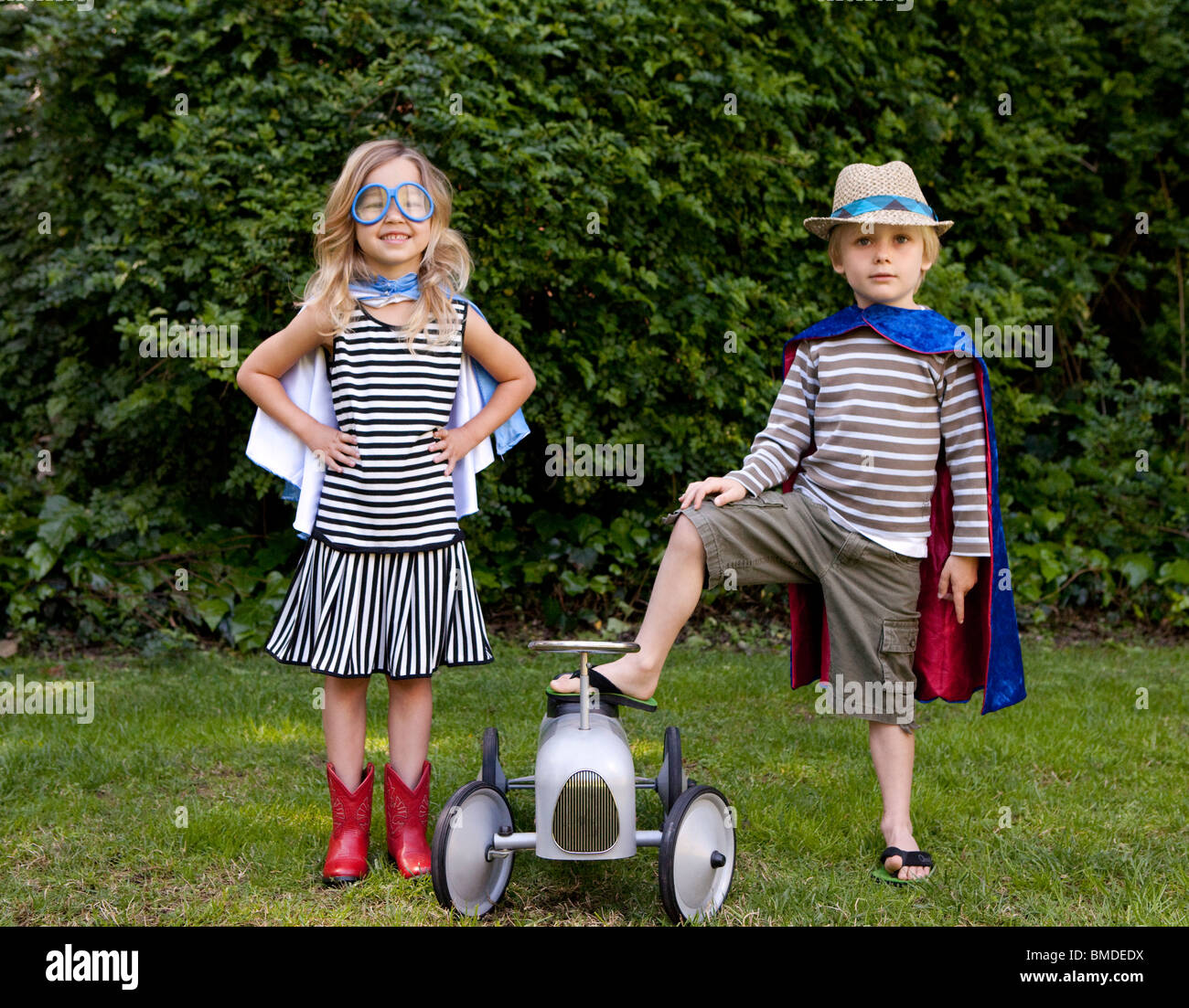 Boy and girl in capes with toy car - Stock Image