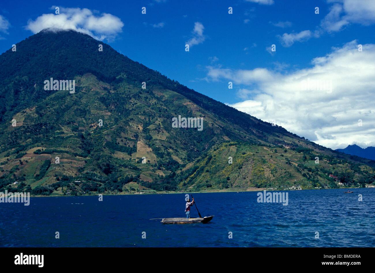 Maya man poling a boat on Lake Atitlan, Guatemala - Stock Image