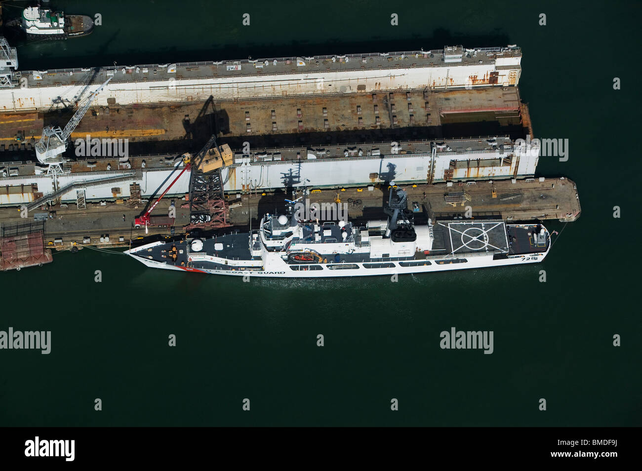aerial view above United States Coast Guard cutter docked adjacent to San Francisco drydock - Stock Image