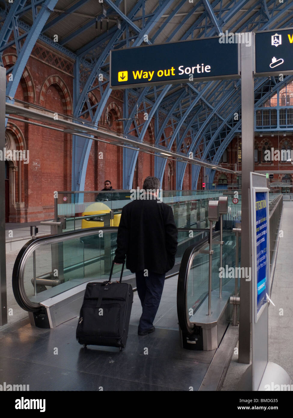 Man boarding the exit escalator from Eurostar at St Pancras Station - Stock Image