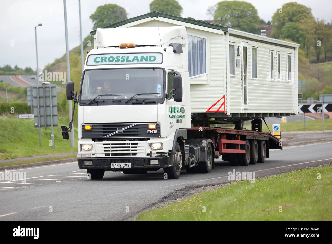 Traffic on the A75 wide or abnormal load static caravan on the back of a articulated lorry Scotland UK - Stock Image