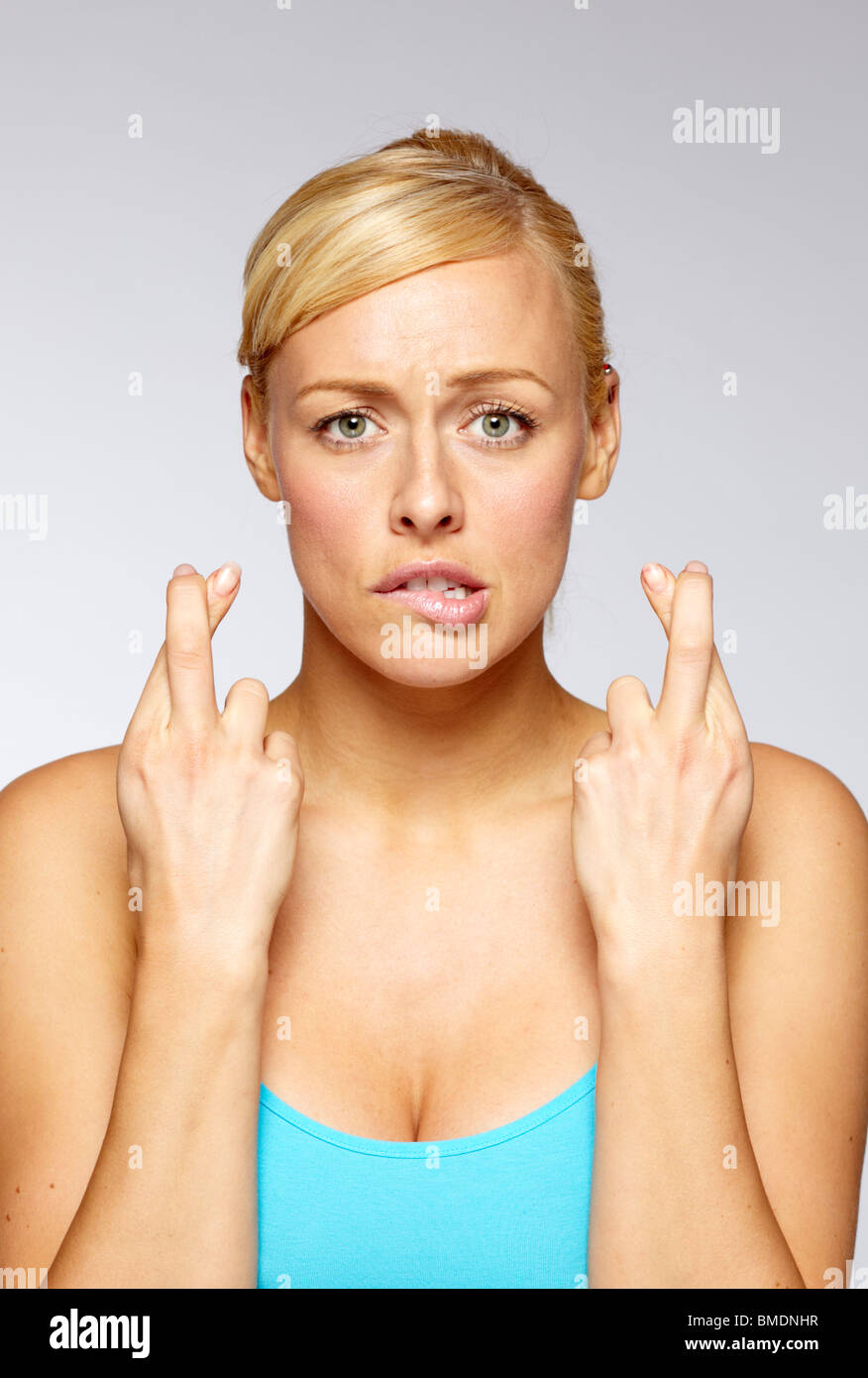 Woman with fingers crossed - Stock Image