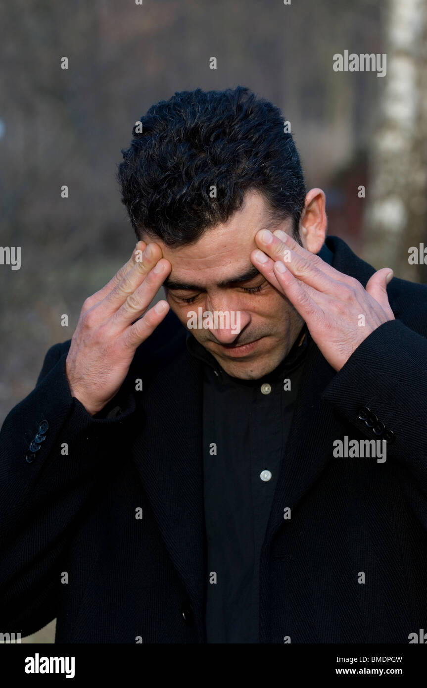 Portrait of a Middle Eastern man head in hands Berlin Germany - Stock Image
