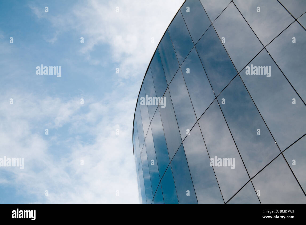 Modern round building reflecting the sky and clouds. - Stock Image