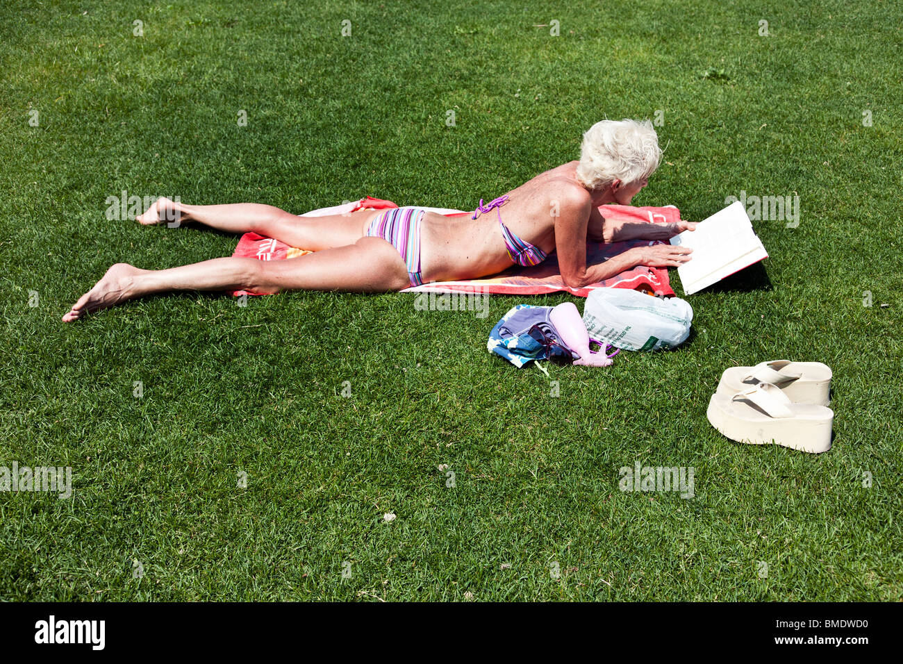 shapely older woman with taut skin wearing a bikini lies on towel in grass  sunbathing at