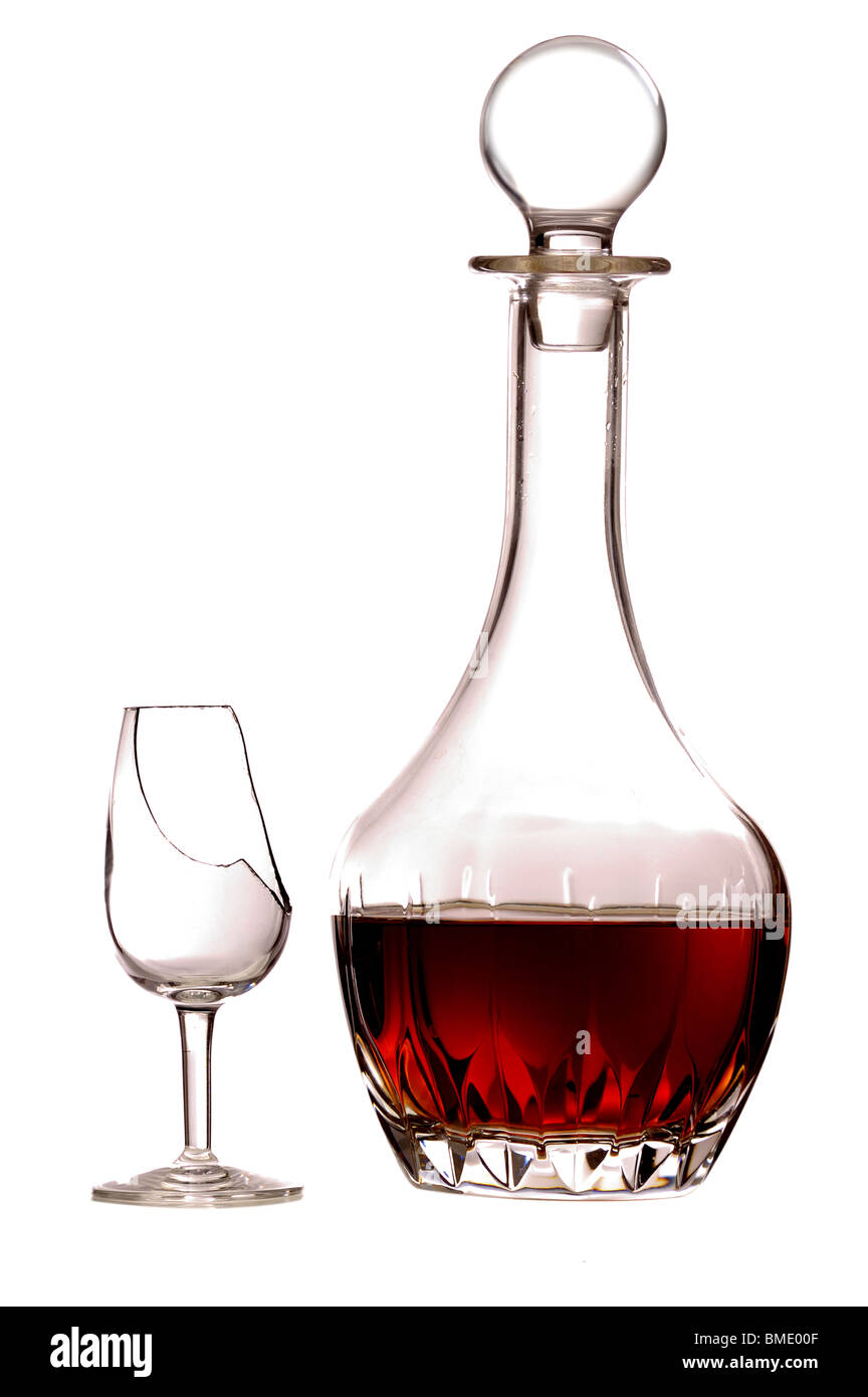 A decanter of sherry and an empty broken glass, isolated on a pure white background. - Stock Image