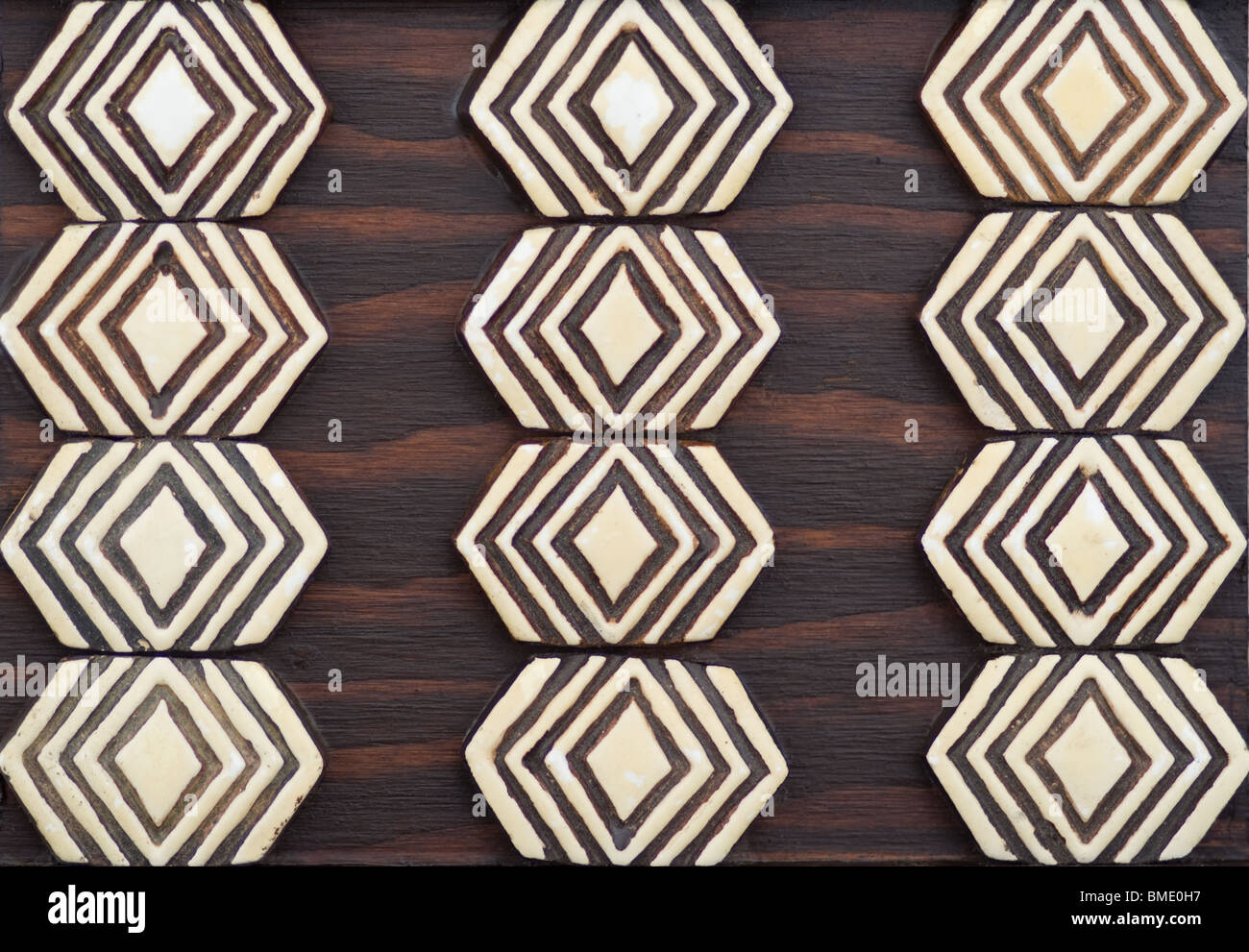 Tribal geometric primitive jungle brown wood and ivory color art trivet - Stock Image
