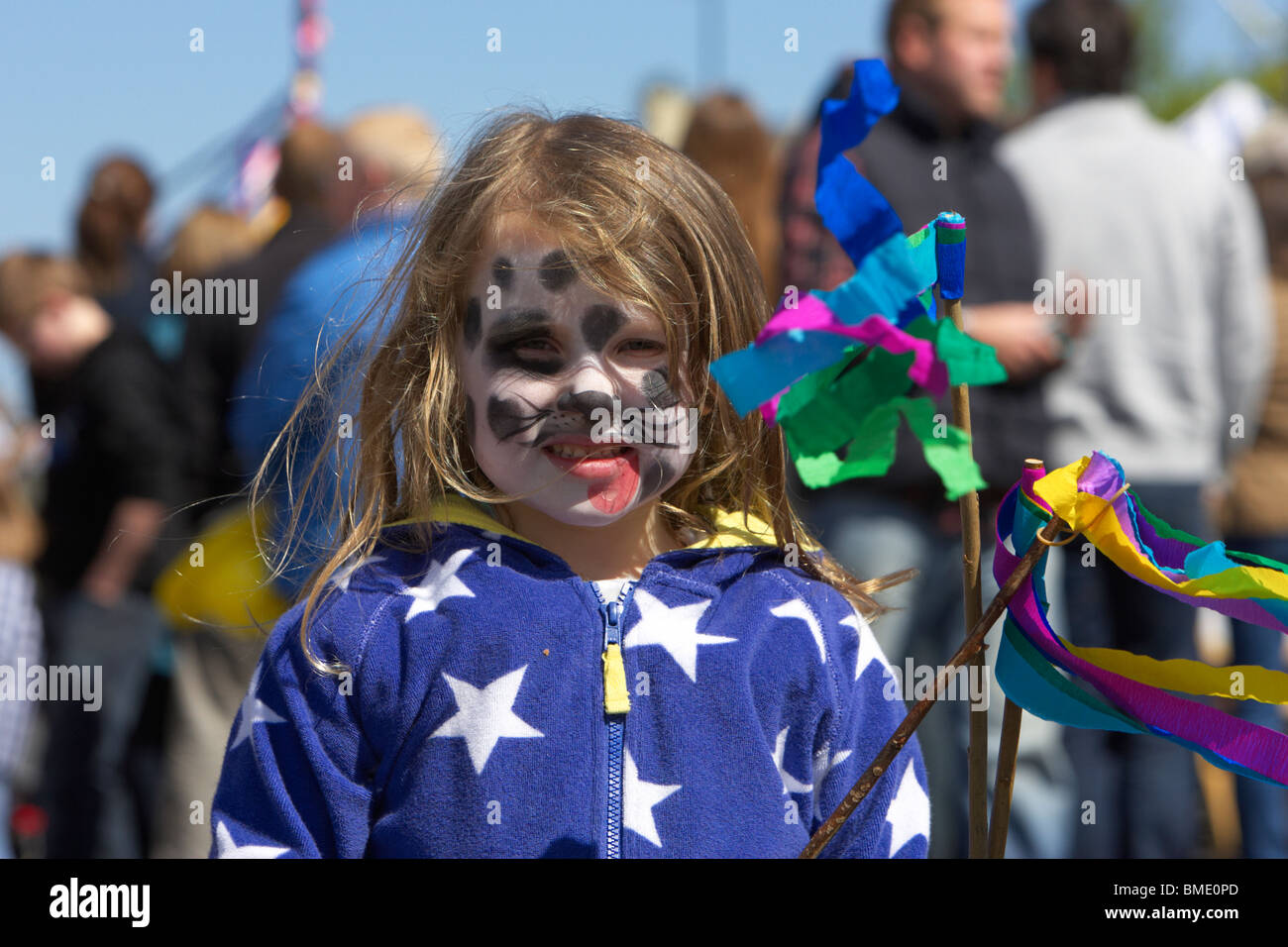 young girl with face painted holding ribbons at a festival on mayday in holywood county down northern ireland - Stock Image
