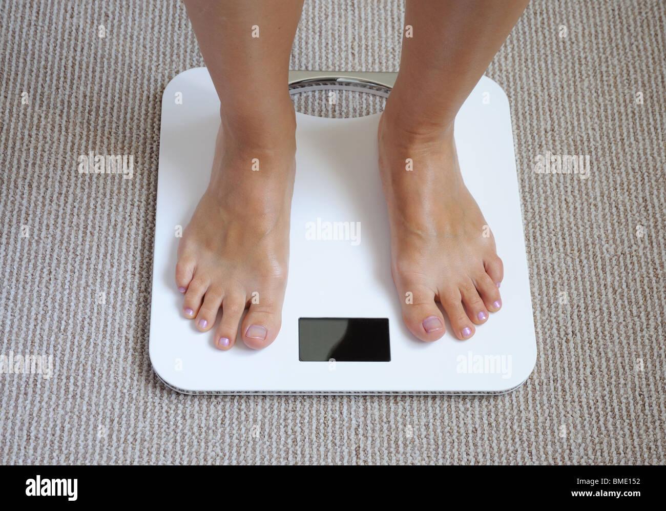 Female feet on bathroom scale - Stock Image