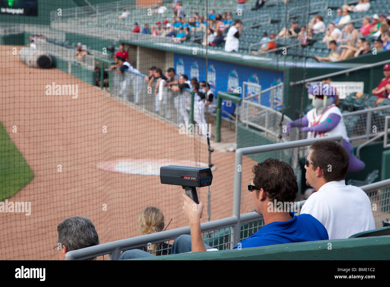 Baseball Scout Uses Radar Gun to Time Pitcher's Speed - Stock Image
