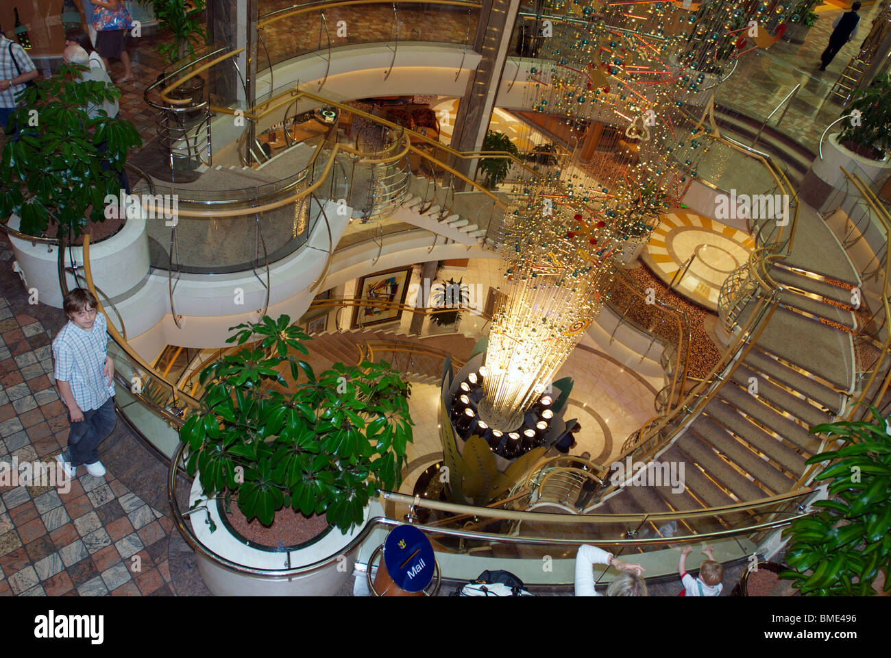 The Royal Caribbean cruise liner the Navigator of the Seas showing the massive main stairway aboard. - Stock Image