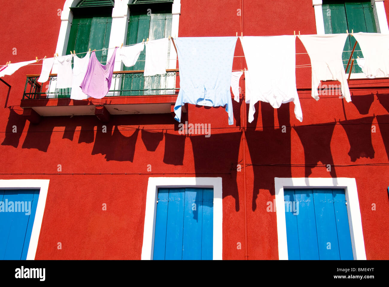 Laundry and clothes hanging out to dry in the streets of Burano, Italy near Venice. - Stock Image