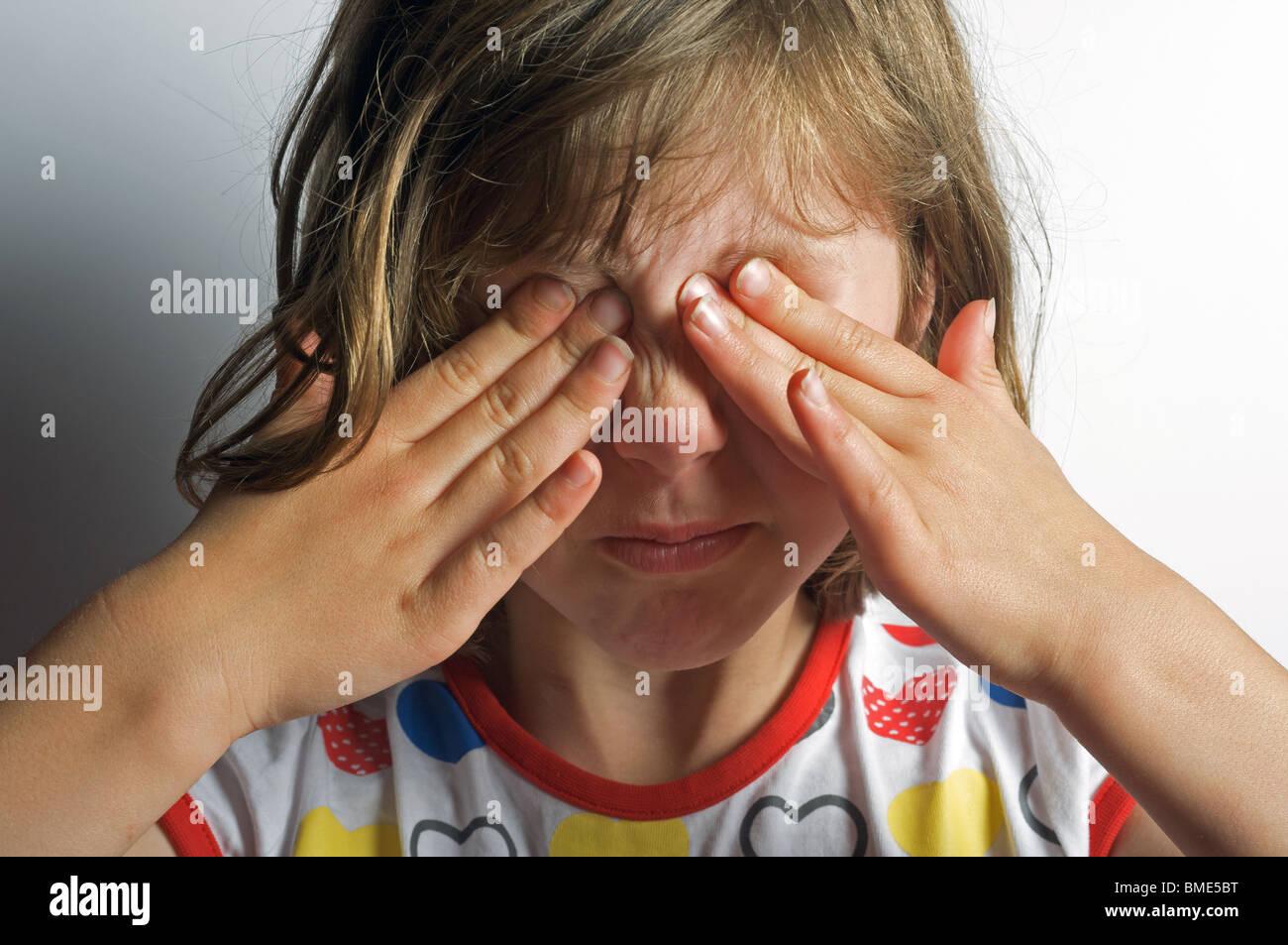 6-year old girl wiping eyes after sobbing - Stock Image