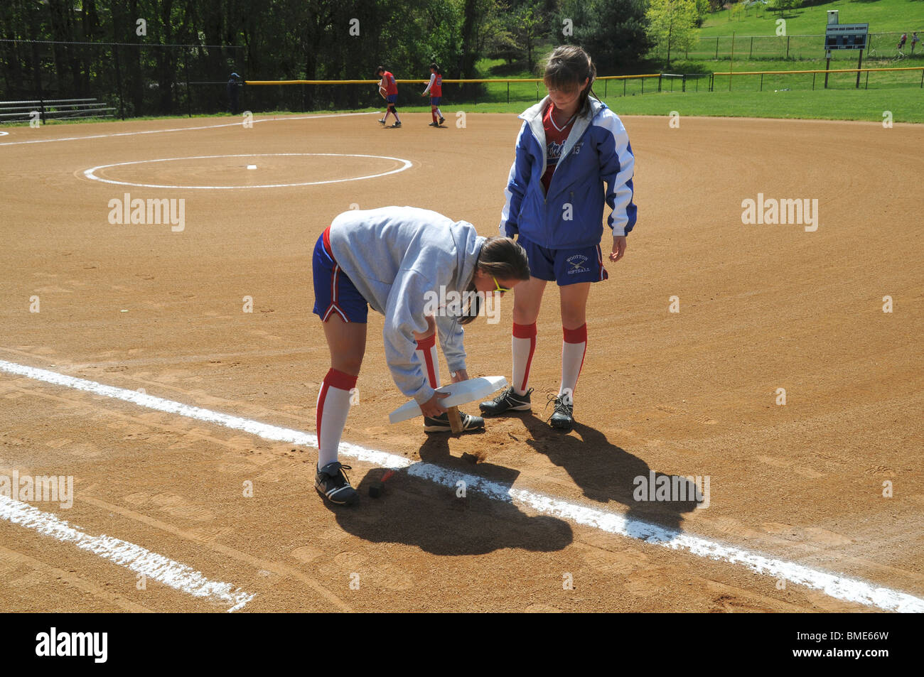 wo girls repair  one of the bases used in a baseball game - Stock Image