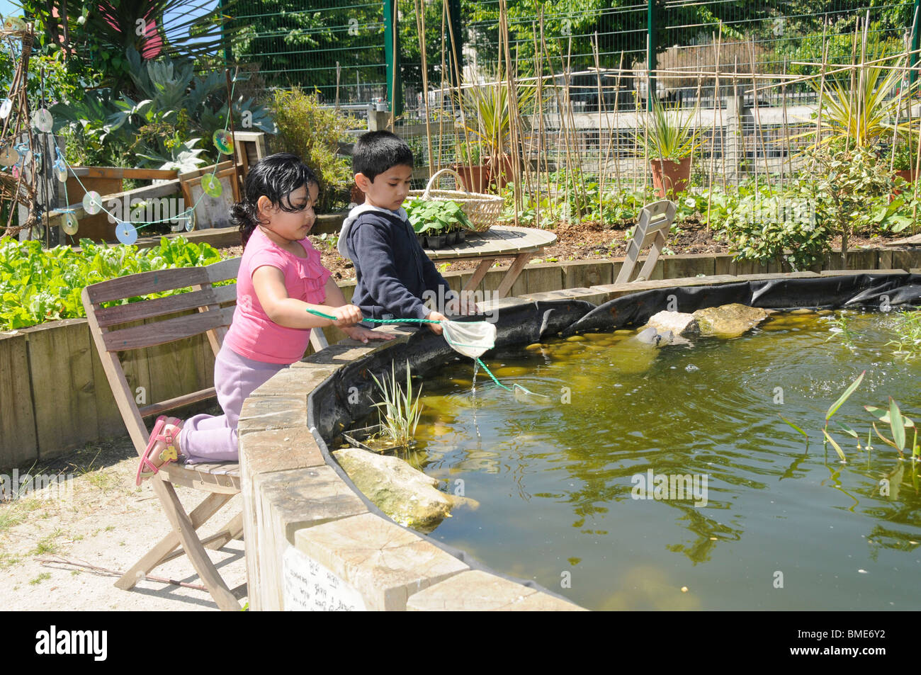 UK BENGALI CHILDREN PLAYING AT POND AT SPITALFIELDS CITY FARM IN LONDON - Stock Image
