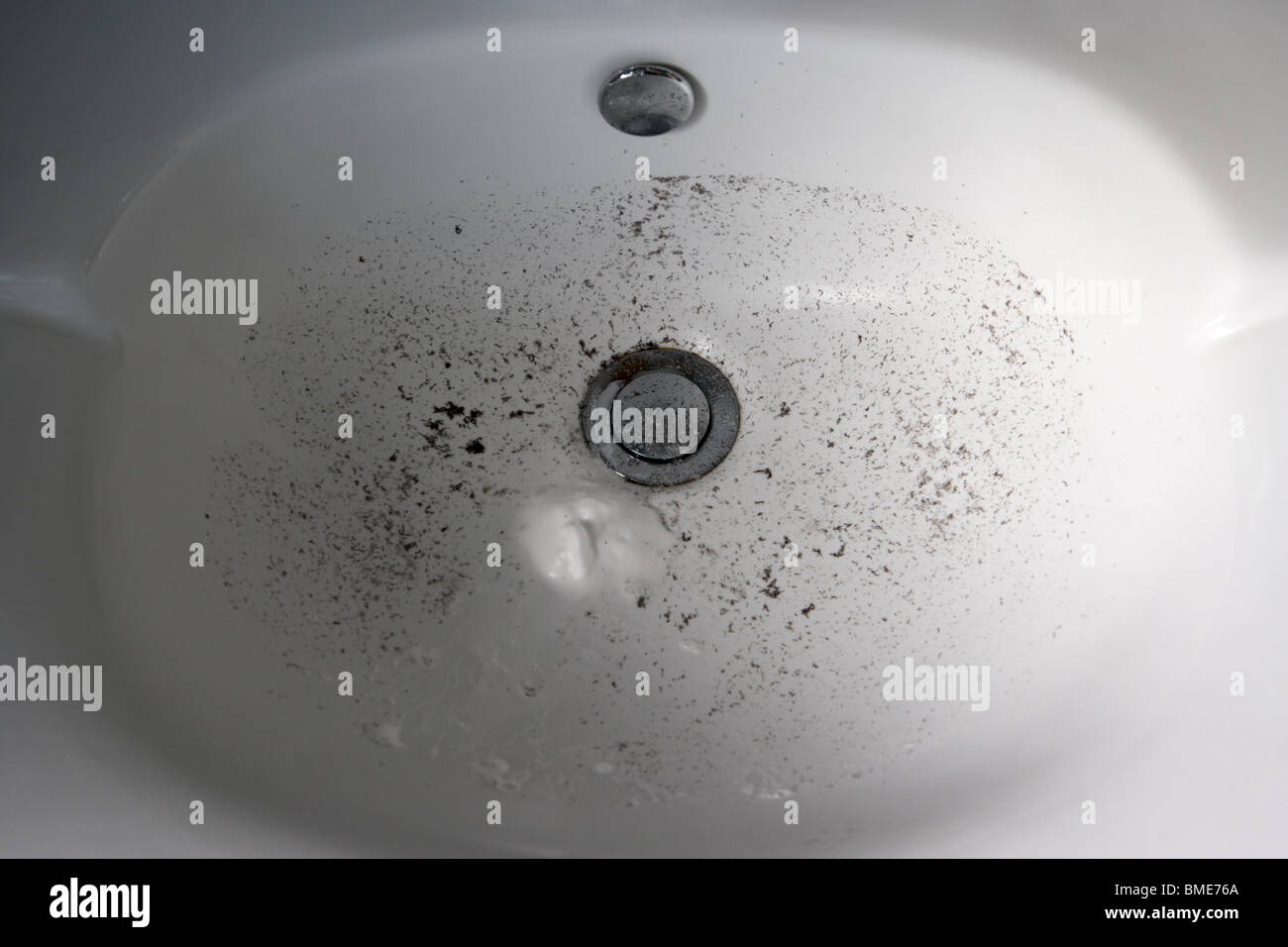 dirty bathroom sink with remnants of mans shaving - Stock Image