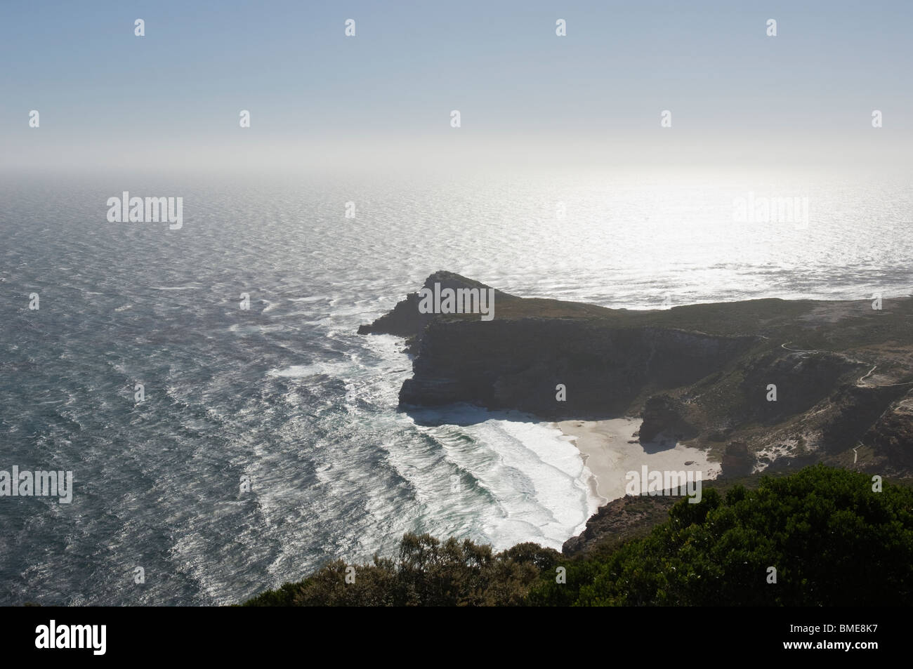 Sunlight over outcrop and ocean - Stock Image