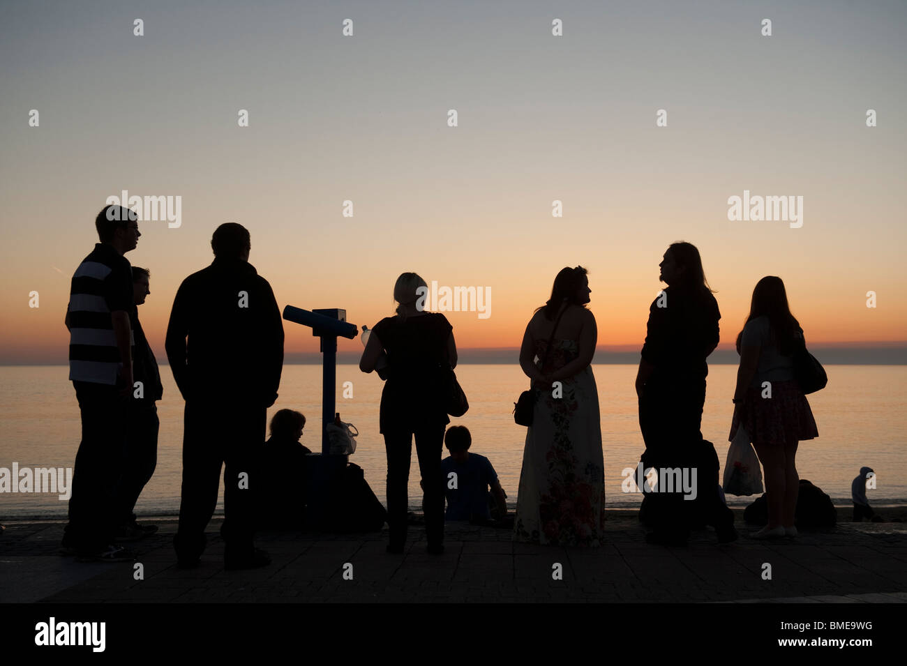 A group of people in silhouette looking at the sunset over Cardigan Bay, Ceredigion west Wales UK - Stock Image