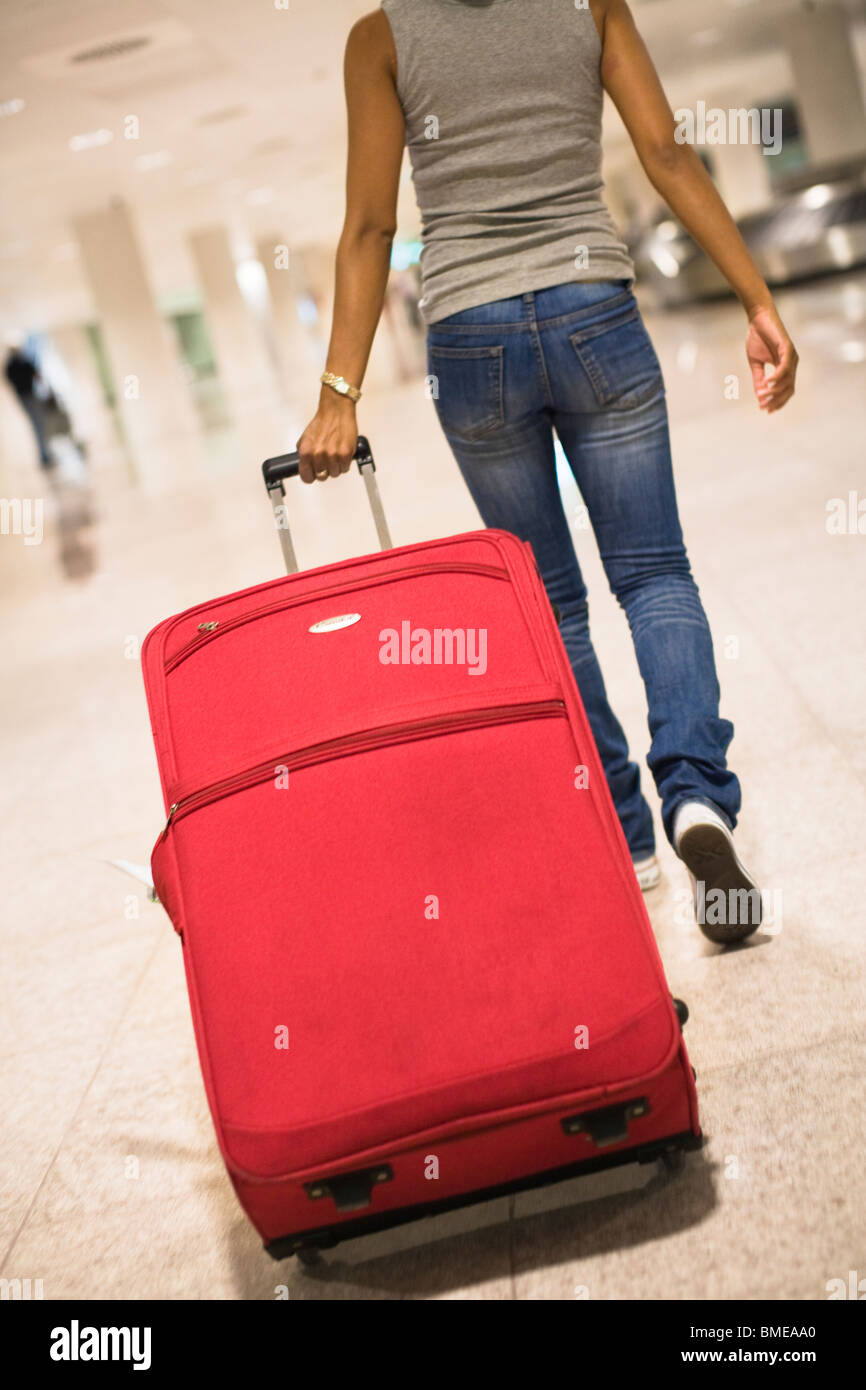 Woman with suitcase at an airport - Stock Image