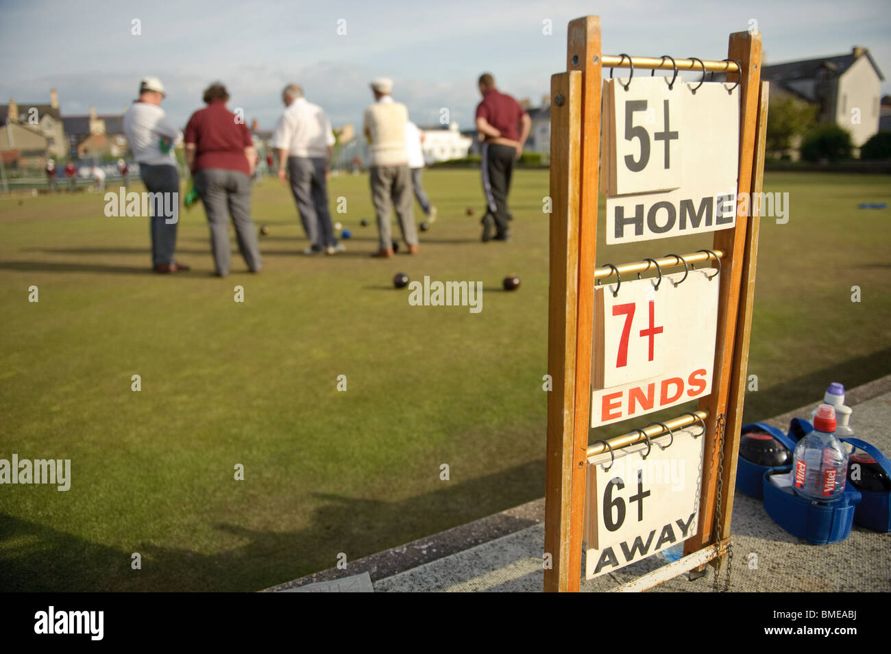 rear view of a group of middle aged men playing a game of lawn green bowls on a summer evening, Aberystwyth Wales - Stock Image