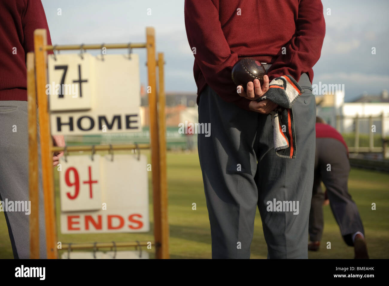 rear view of middle aged Men playing a game of lawn green bowls on a summer evening, Aberystwyth Wales UK - Stock Image