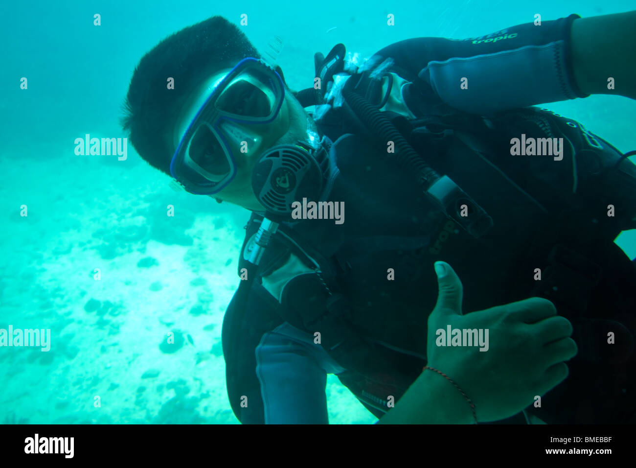 A diver signals OK from outside a tourist submarine underwater Stock Photo
