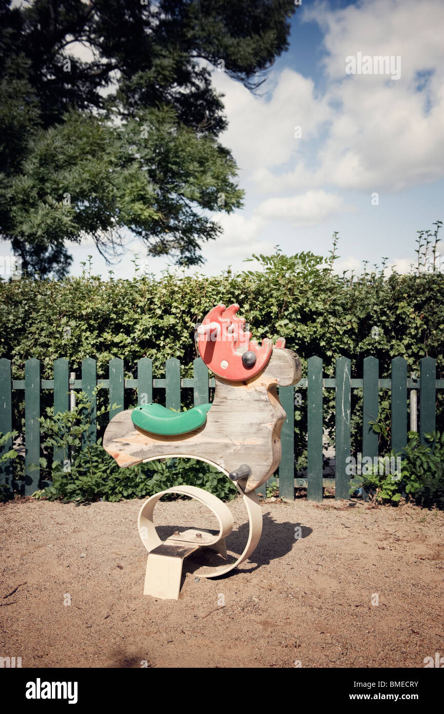Old rocking horse in playground - Stock Image