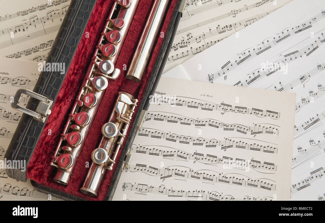 A western concert flute inside its leather and velvet case leant against old music sheets. - Stock Image