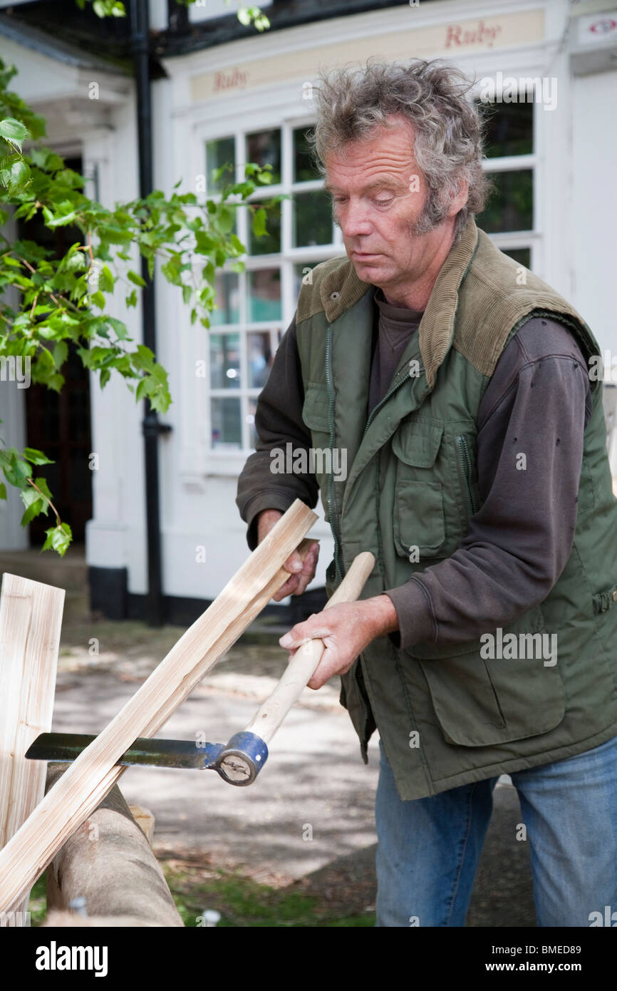Demonstration of preparing fence pales from sweet chestnut at the biennial Charter Fair in Haslemere, Surrey, England. Stock Photo