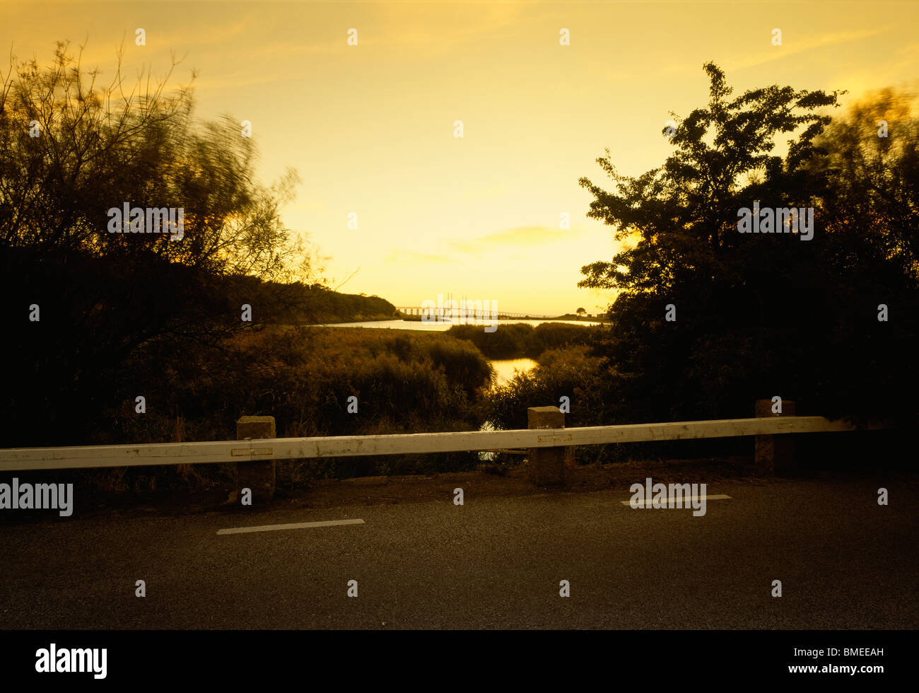 Road with view of river in background at dawn - Stock Image
