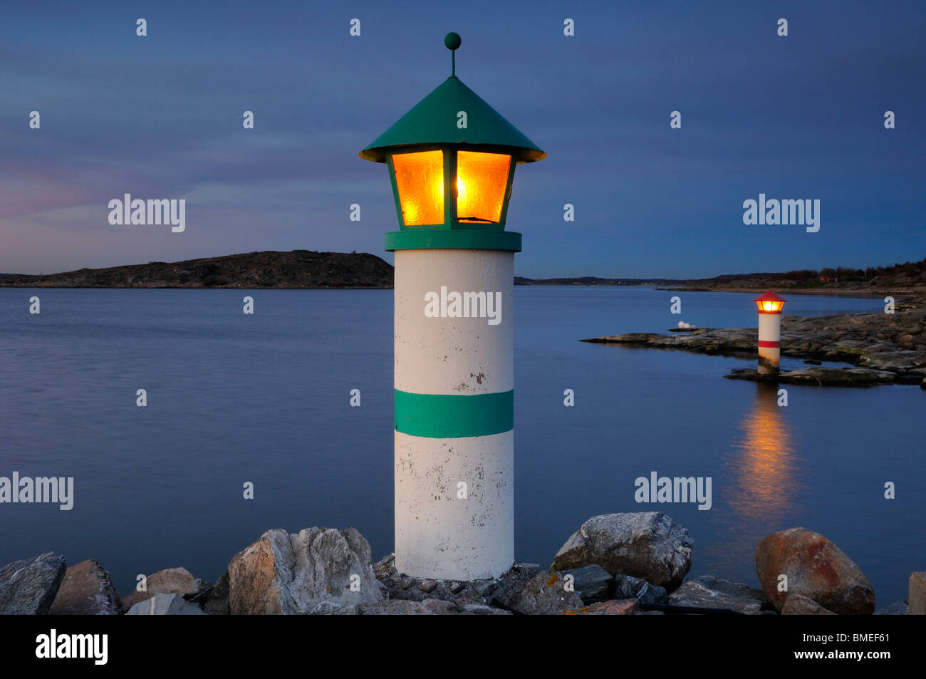 Scandinavia, Sweden, Vastkusten, View of illuminated lighthouse on sea - Stock Image