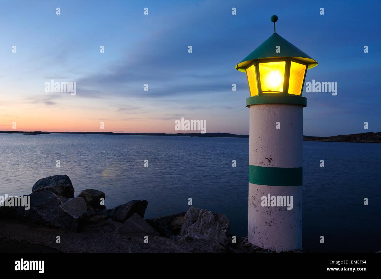 Scandinavia, Sweden, Vastkusten, View of illuminated lighthouse on sea - Stock Image