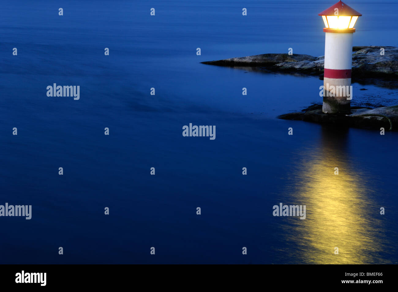 Scandinavia, Sweden, Vastkusten, View of illuminated lighthouse on sea, elevated view - Stock Image