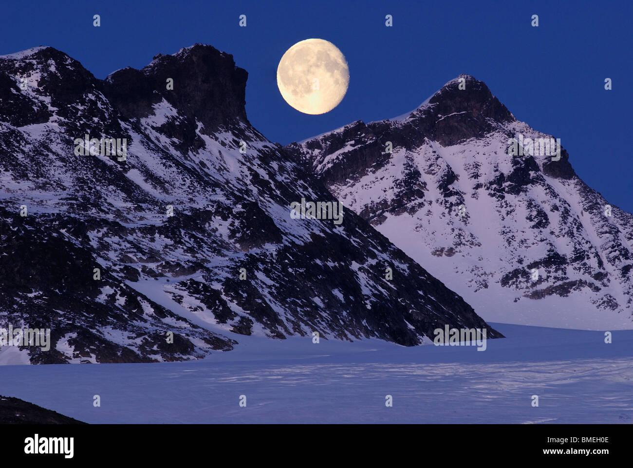 Scandinavia, Norway, Snowcapped mountains with moon in background - Stock Image