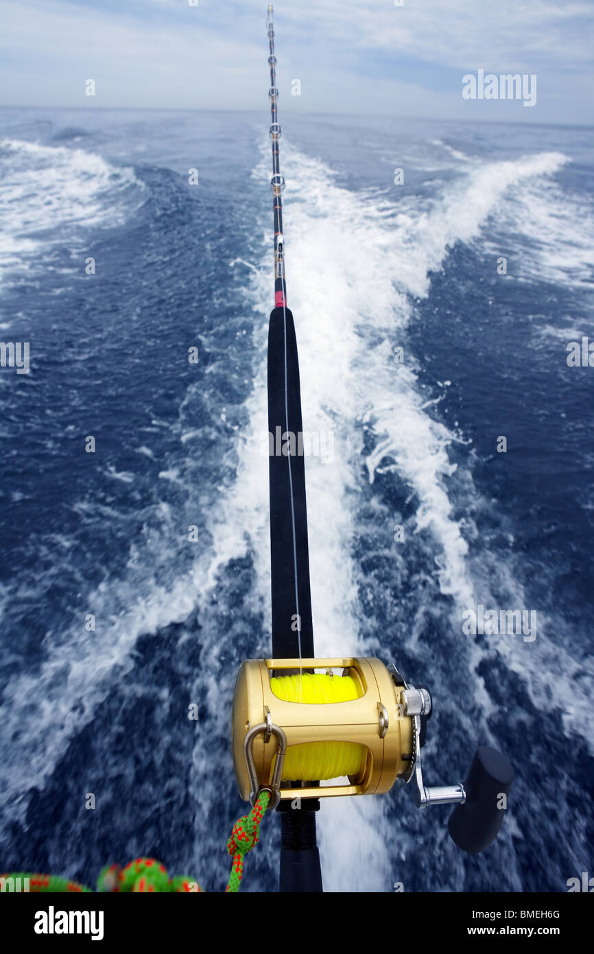 fishing big game rod and reel on boat wake prop wash - Stock Image