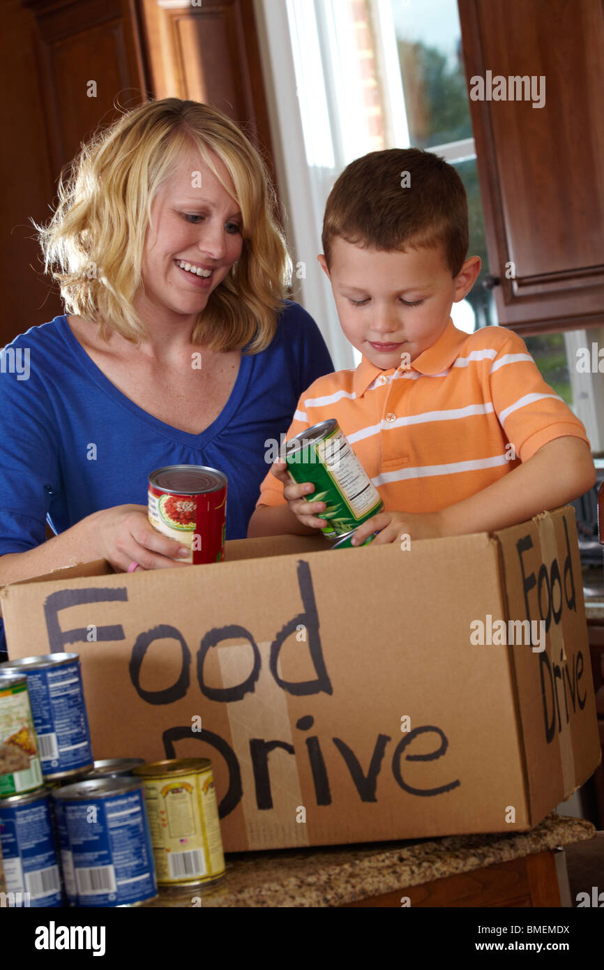 A Mother And Son Collecting Food For A Food Drive - Stock Image