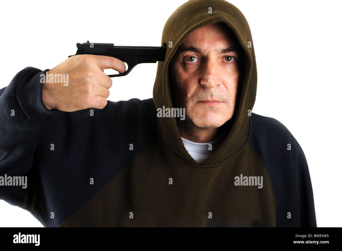 A man wearing a hood aiming a gun with white background - Stock Image