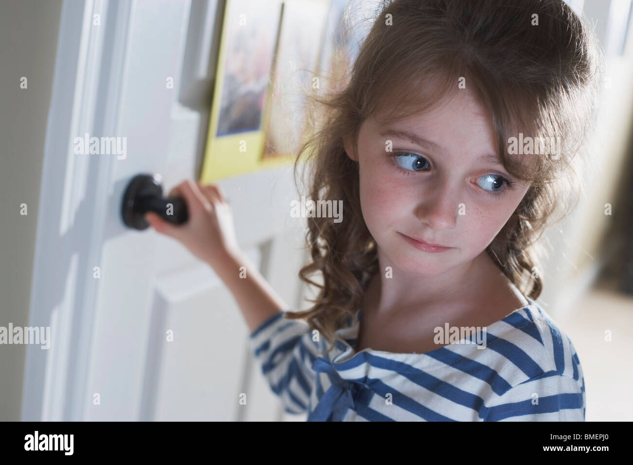 A Girl Turning A Doorknob To Leave - Stock Image