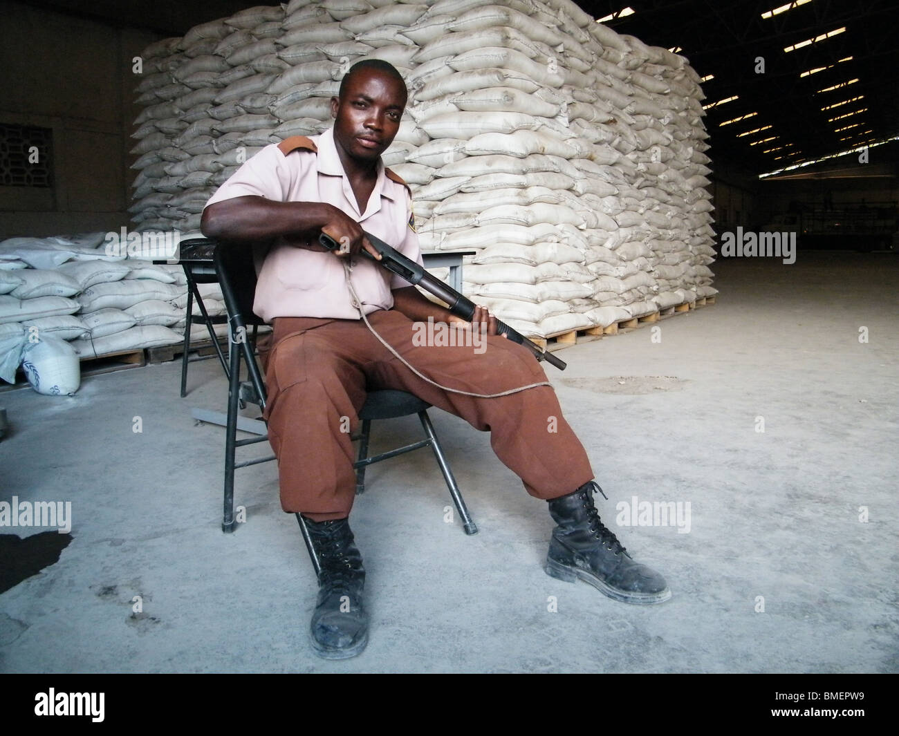 An armed man guards the entrance to a World Food Program warehouse full of donated food aid, Gonaives, Haiti - Stock Image