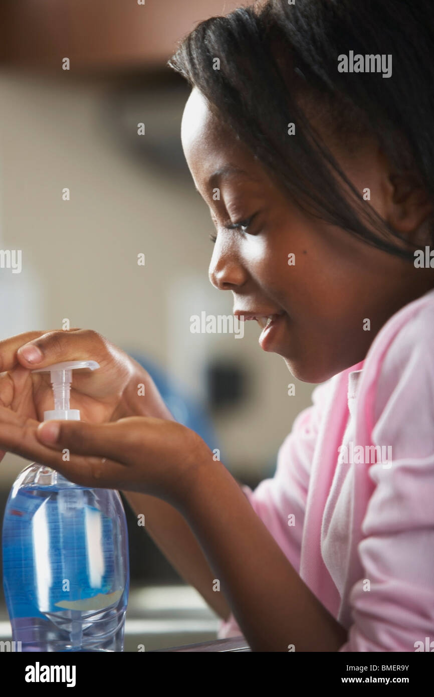 A Girl Pumping Soap To Wash Her Hands - Stock Image