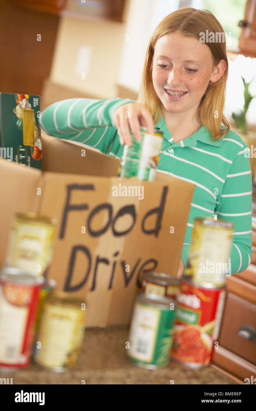 Putting Canned Food In A Box For A Food Drive - Stock Image