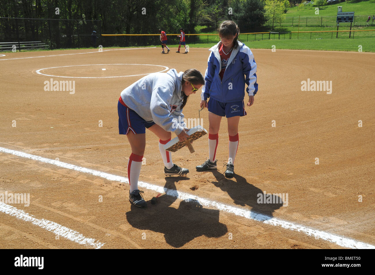 Two girls repair  one of the bases used in a baseball game - Stock Image