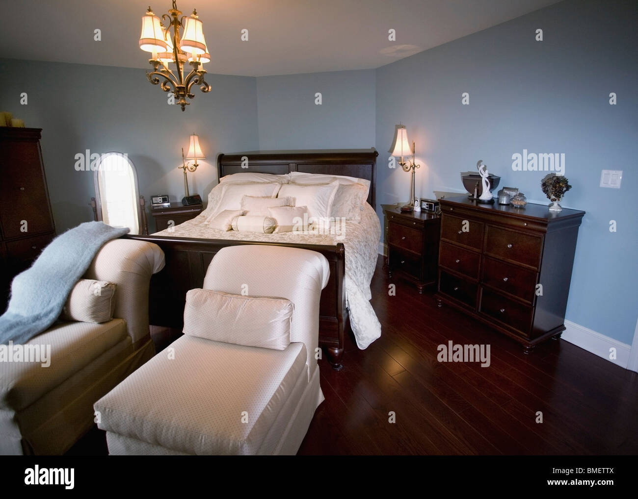 - A Bedroom With Chaise Lounge Chairs At The Foot Of The Bed Stock