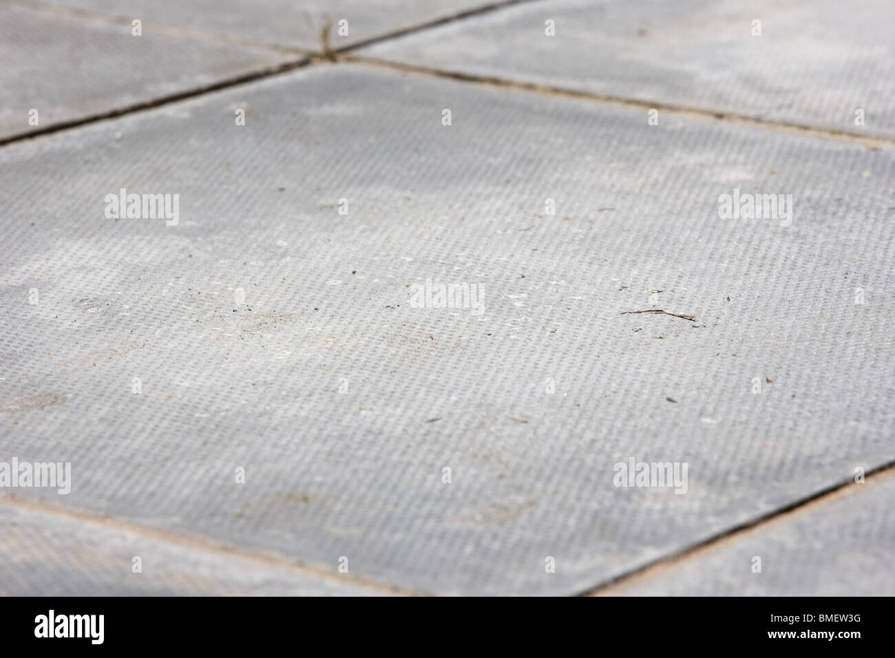 square concrete paving slab laid as a garden patio in the uk - Stock Image