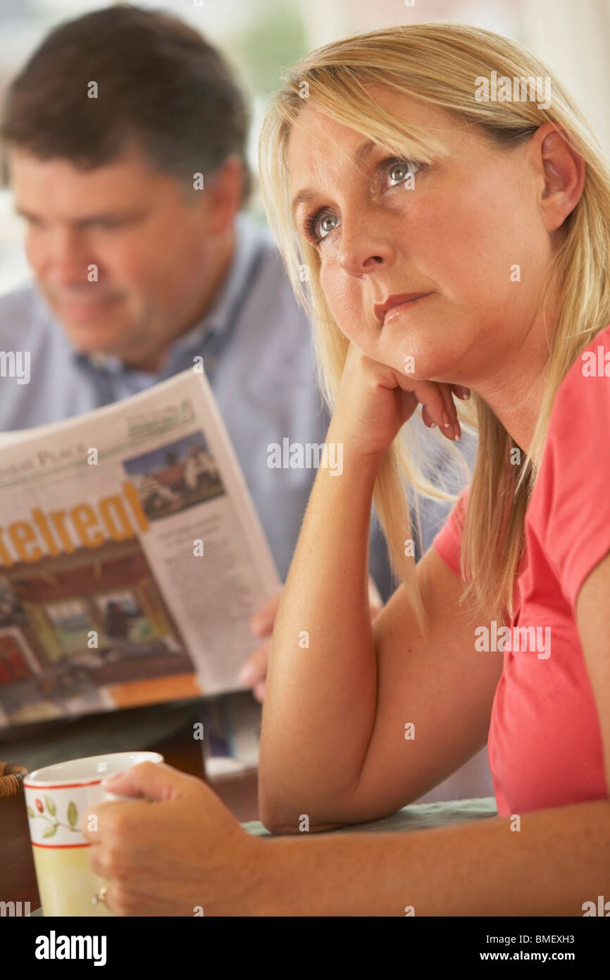 A Wife Ignored By A Husband Reading The Newspaper Stock Photo