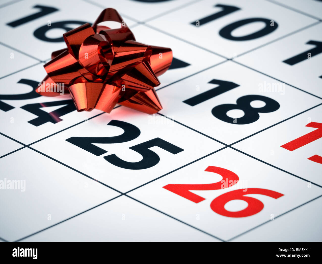 Close up of a red bow on a calendar page. - Stock Image